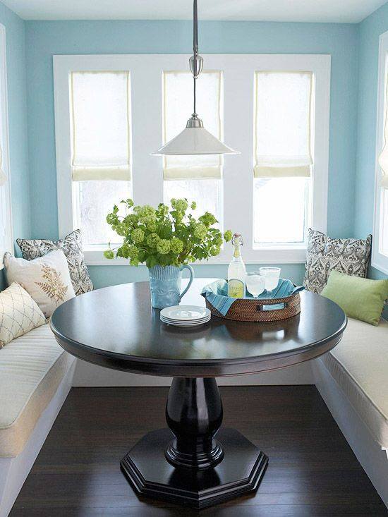 Blue breakfast nook features a built-in seating surrounding the dark wood dining table lighted by a white dome pendant.