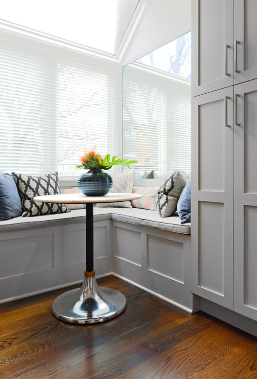 This breakfast nook showcases a sleek round dining table and built-in seating filled with fluffy pillows. It has hardwood flooring and glass windows covered in white blinds.