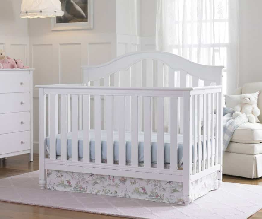 Nursery room with white walls and white furniture along with a light purple rug set on the hardwood flooring.