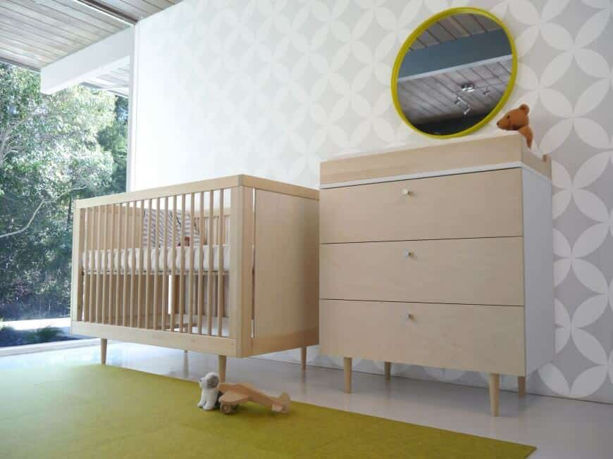 Nursery room with stylish walls and a rug set on smooth white flooring.
