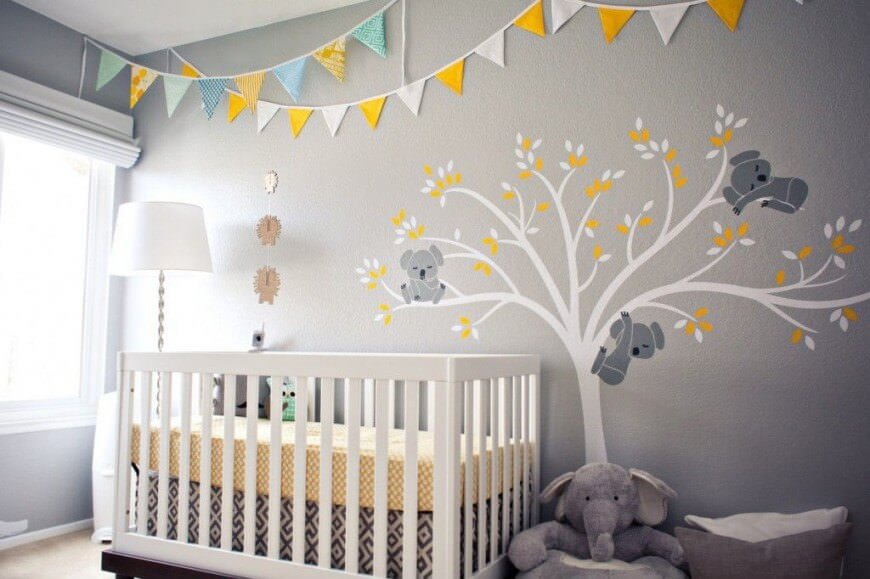 Nursery room with gray walls designed with a cute tree.