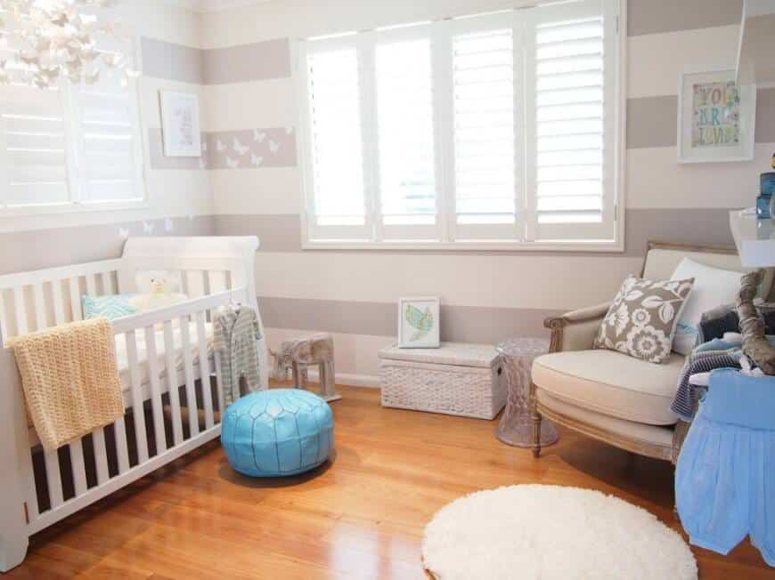 Nursery room with gray and white patterned walls and a hardwood flooring lighted by a cute chandelier.