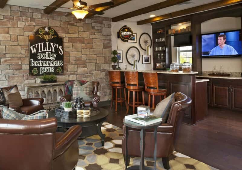 Smallish man cave with custom built dark wood bar area with hotel lobby like lounge area to enjoy a cold one. The stone accent wall creates a textured and thematic design along with the dark wood beamed ceiling.
