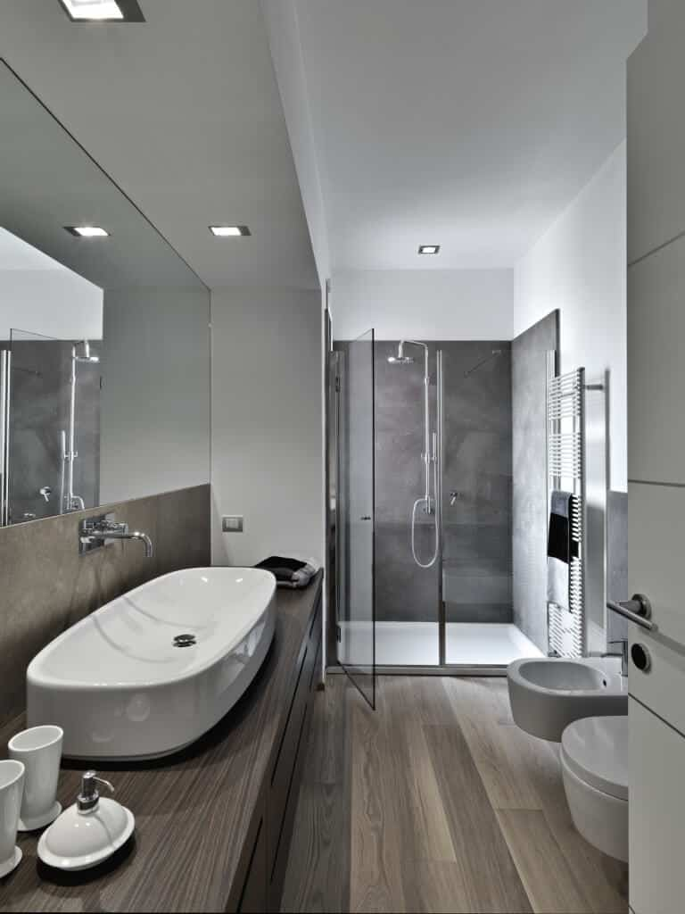 This bathroom is absolutely stunning with its cool toned ashy colors. The white ceramics are brought to life through gray tiles in the shower and gorgeous hardwood tiles and countertops. This is truly a sleek and contemporary design at its finest.