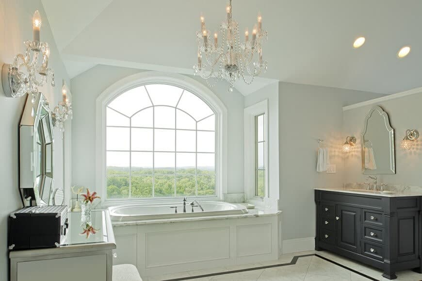 White primary bathroom with two vanities facing each other paired with arched and octagon mirrors. There's a soaking tub in the middle and beneath the glazed window with a green outdoor view.