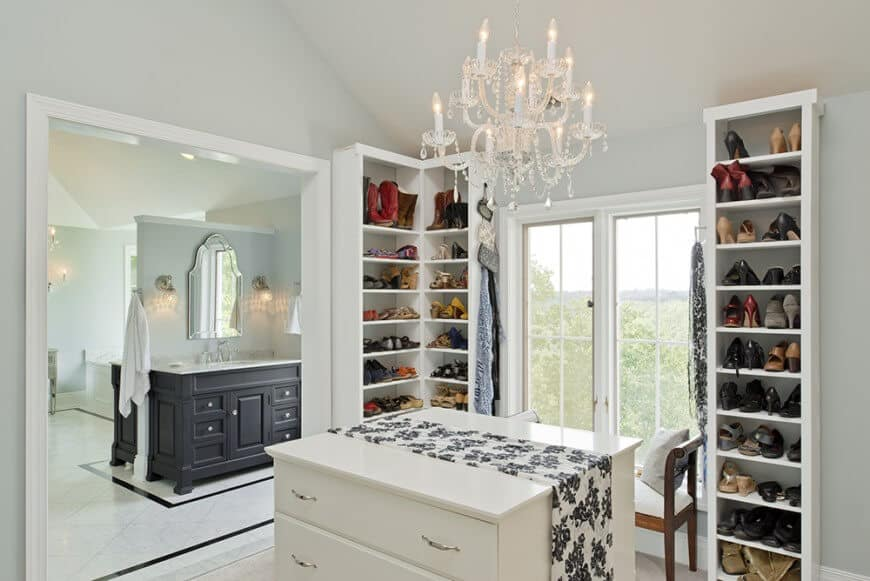 White bedroom closet boasting a small center island with smooth countertop. The cabinetry matches well with the white walls while the elegant chandelier looks so gorgeous.