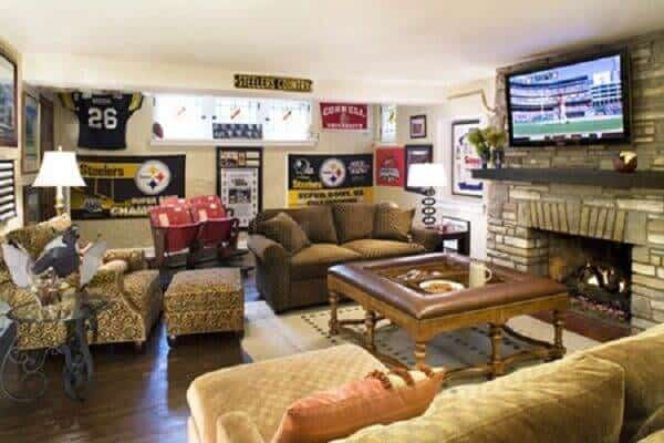 Comfortable man cave with sectional sofa, armchair and loveseat surrounding a fireplace with TV mounted above. I love that taller than average coffee table that could double as a huge ottoman. Loads of sports memorabilia adorn the walls.
