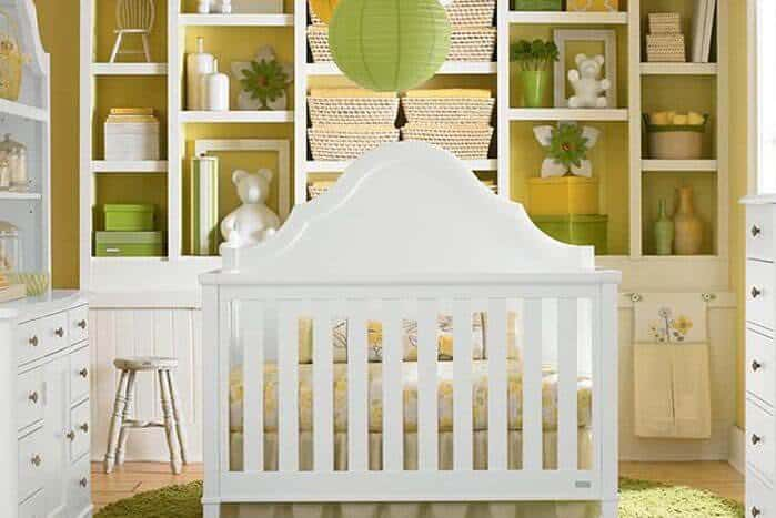 Small nursery room with multiple shelves lighted by a cute pendant lighting.