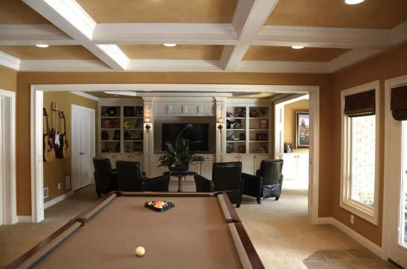 A game room with black seats in front of the TV lighted by wall lights. There's a billiards pool on the back. The room's ceiling looks stunning as well.