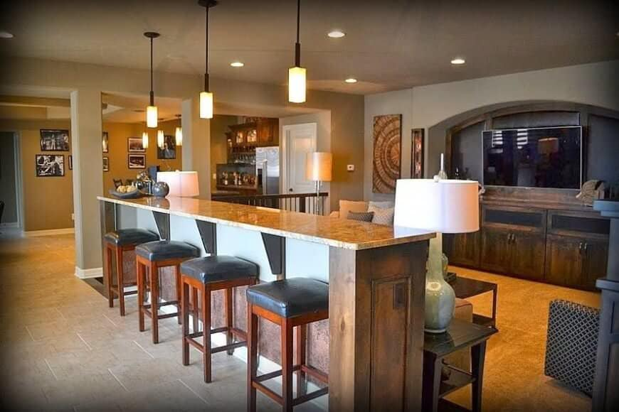 A large bar with a long counter with marble countertop lighted by a lovely set of pendant lights.