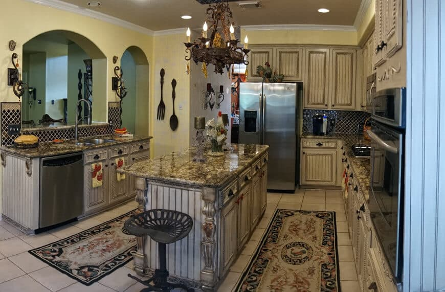 An elegant kitchen set with a glamorous chandelier, stunning rugs and beautiful counters and countertops.