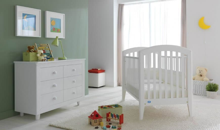 Nursery room with smooth white and green walls along with a rug.