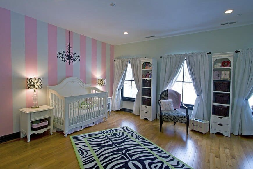 This nursery room is very organized. There's a couple of shelves near the baby's crib. The hardwood flooring is topped by an eye-catching zebra style rug while the pink and white wall colors are just perfect.