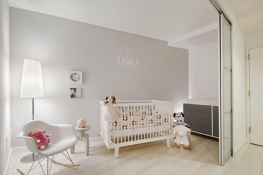 Nursery room with light gray finished walls lighted by a floor lamp.