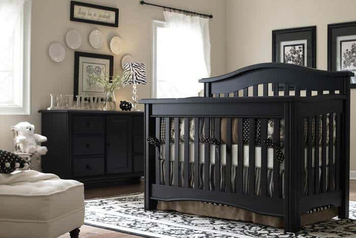 Nursery room featuring a classy espresso finished tables, picture frames and bed frame.