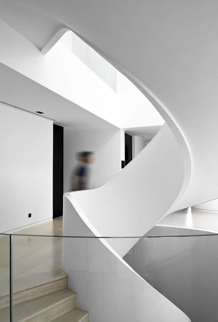 Contemporary landing with spiral stairway, wooden floor and glass stair railing.