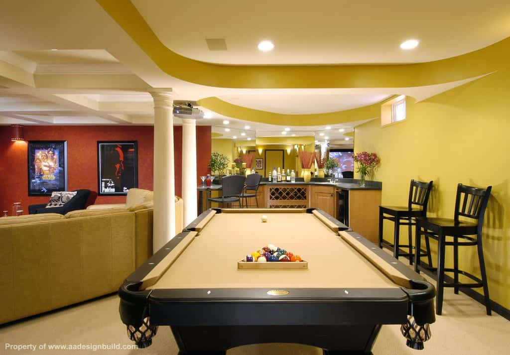 This living room boasts a theater area, an elegant black billiards pool with beige cloth and a bar area lighted by classy ceiling lights.