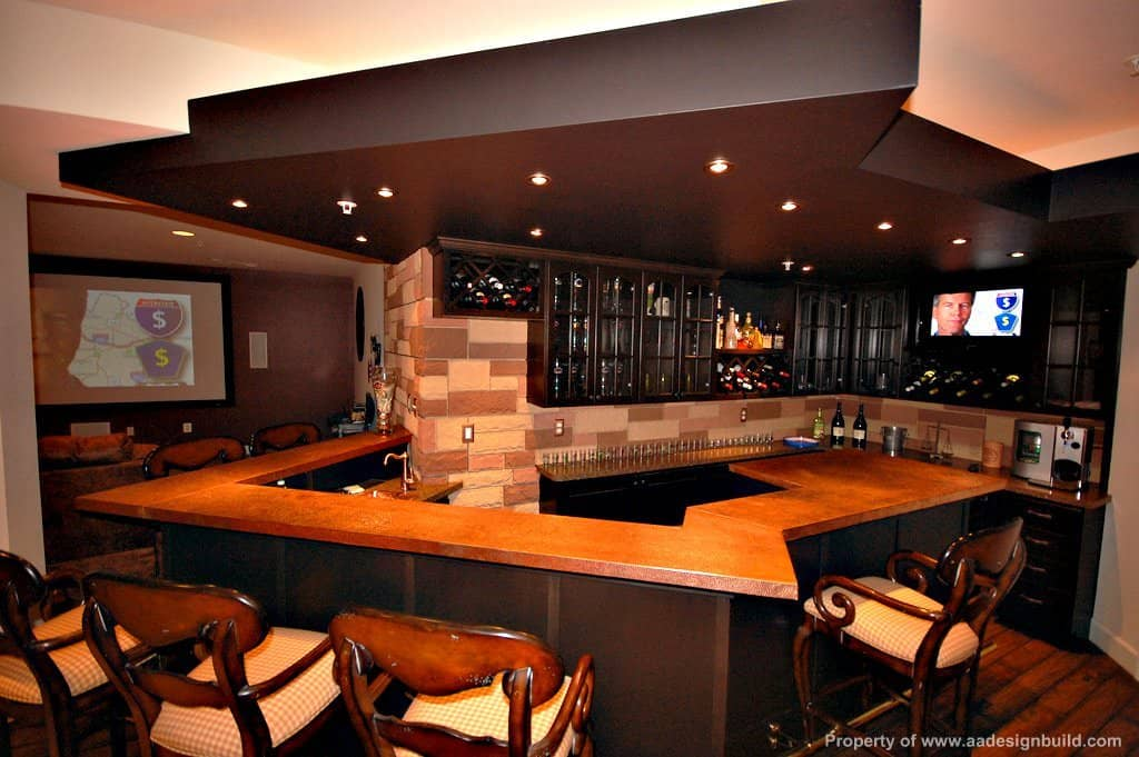 Large bar with a stylish counter and classy bar stools set on the hardwood flooring and lighted by recessed ceiling lights.