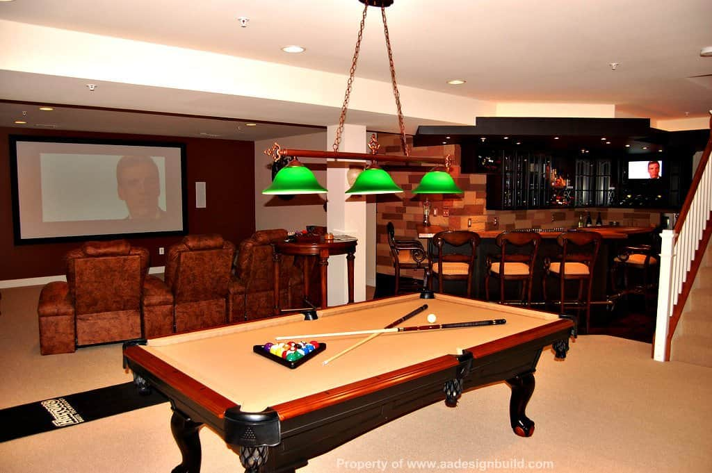 Large man cave boasting a classy bar area and an open theater set up with cozy seats. There's a billiards pool as well, lighted by stylish pendant lighting.