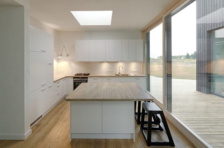 An airy white kitchen with glass walls, skyline ceiling, huge breakfast island with dark wooden benches and white tiles backsplash.