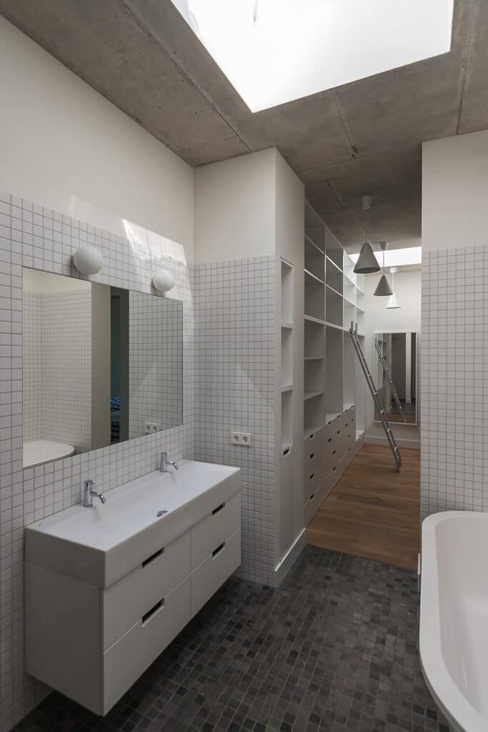 Small primary bathroom with black tiles floors and large vessel sink. There's a doorway leading to the home's closet.