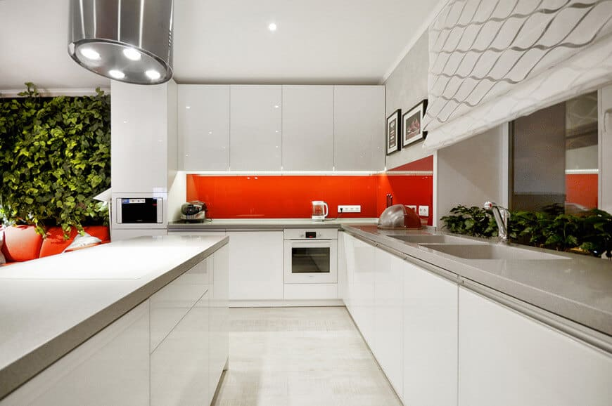 Modern kitchen with a galley layout. It is filled with glossy cabinetry and white oven accented with a vibrant red high gloss backsplash.