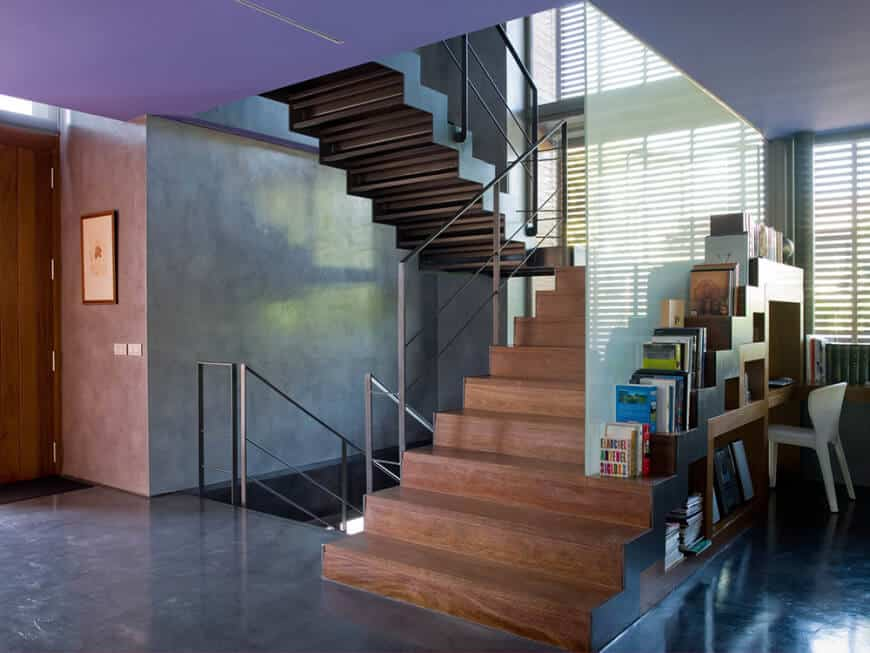 Contemporary landing with plain wood stairs, steel hand railing and a glass partition with a welcoming reading nook.