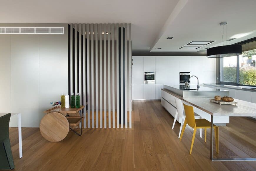 L-Shaped kitchen with white walls accented by vertical concrete bars, long wooden island table with white and yellow chairs, stainless countertops and black oversized lighting hanging from a drop ceiling.