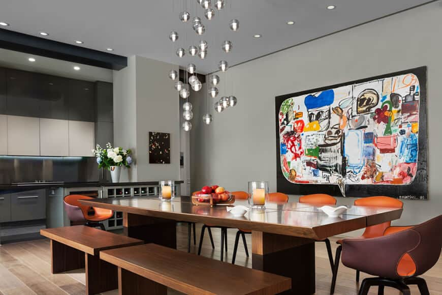 A dining space lighted by crystal globe lamps over a long rectangular table paired with mismatching dining chairs.