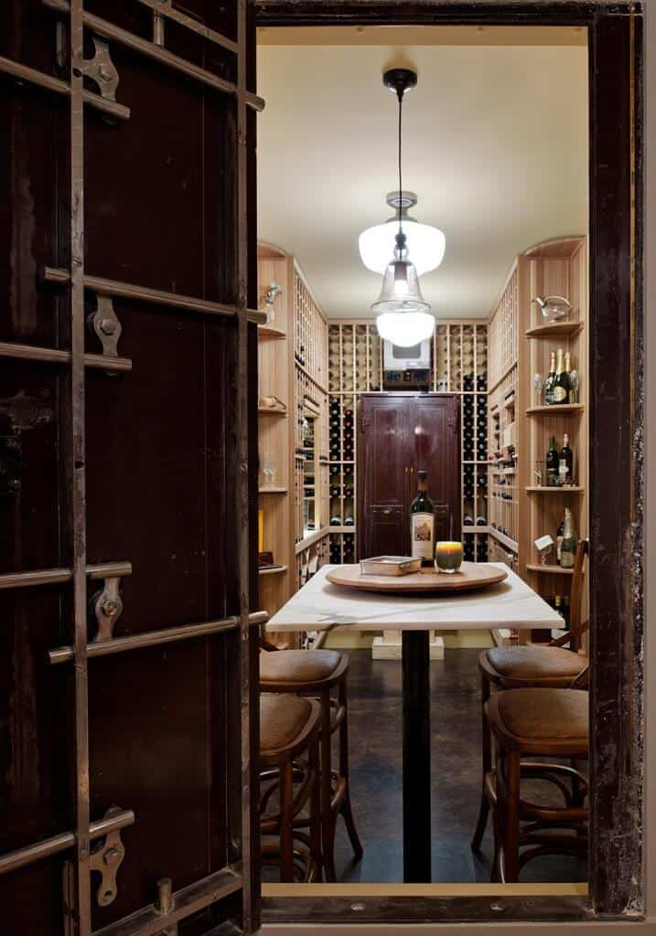 A narrow wine cellar with built-in wooden racks and shelves along with a marble top tasting table paired with cushioned chairs.