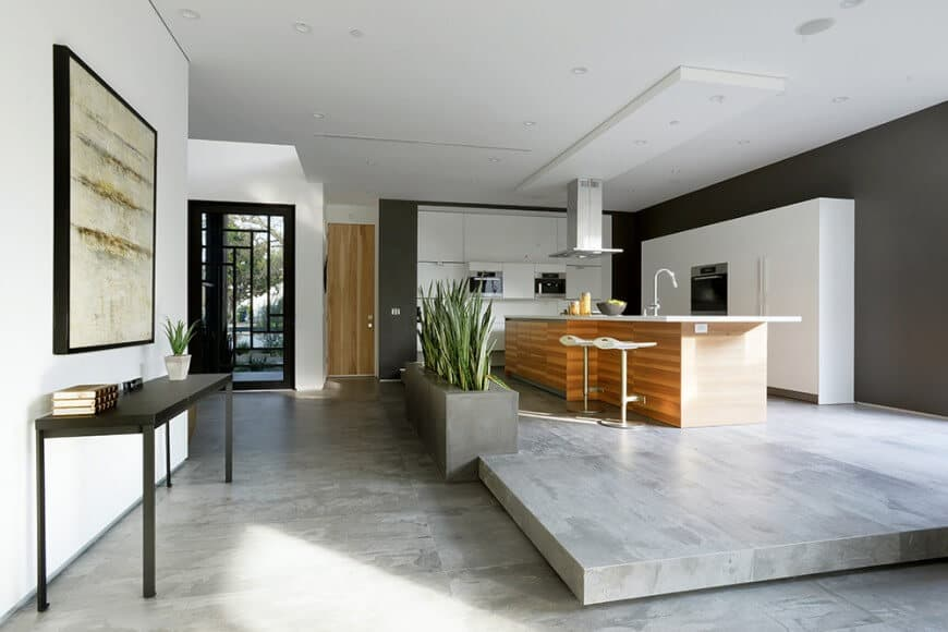 Contemporary kitchen featuring black walls and a platform-style gray flooring. It has a center island with a small breakfast bar area.