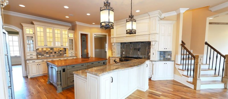 Craftsman-style kitchen interior with two islands, pantries, and pendant lighting.