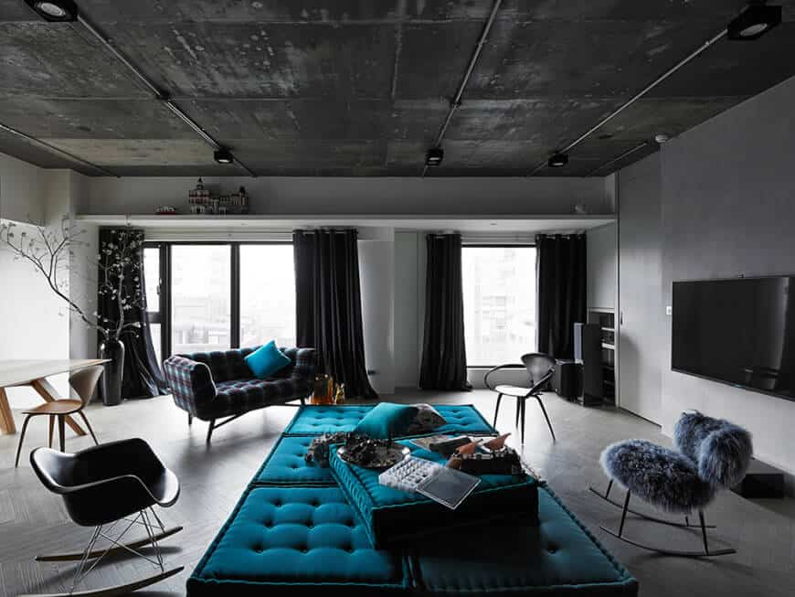 Dark living room accented with a tufted blue ottoman and throw pillow that lays on a checkered couch. It has glass windows covered with black draperies.