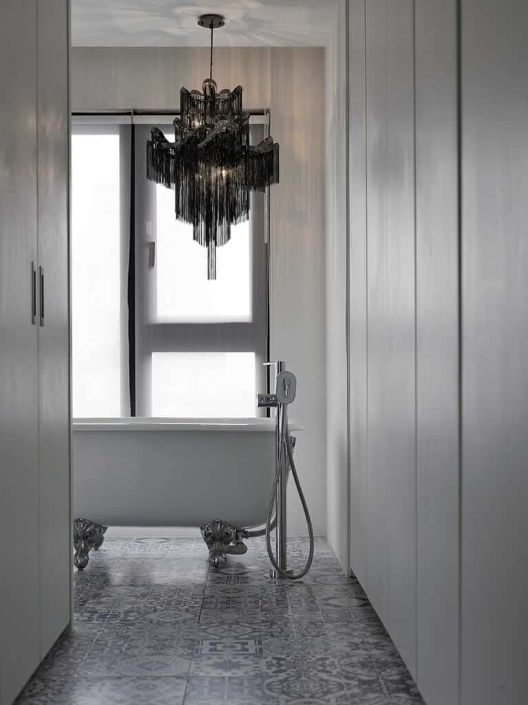 An interesting black chandelier hangs over the clawfoot bathtub in this primary bathroom with full height storage cabinet and patterned flooring.