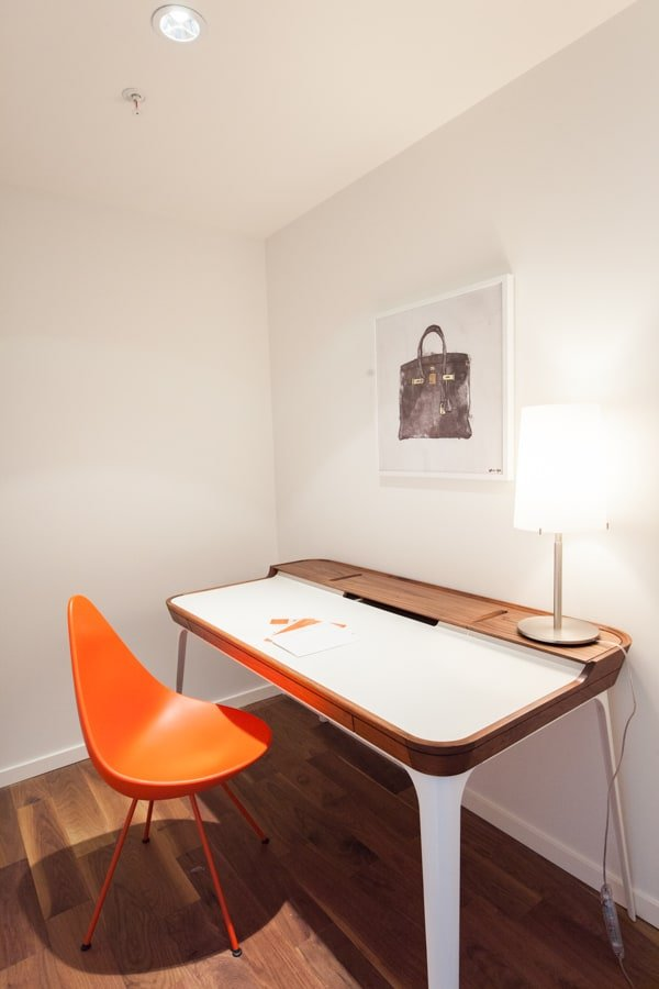 Cool modern minimalist home office with cool modern writing desk and orange chair in an otherwise all white space with hardwood flooring. It doesn't get simpler than this yet looks good.