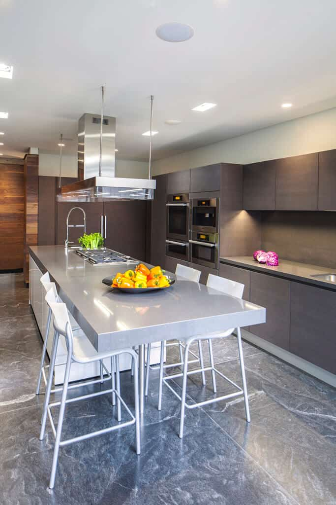 This contemporary kitchen features a very stylish flooring that matches well with the brown cabinetry. The long center island offers a personal space, serving as a dining nook or breakfast bar.