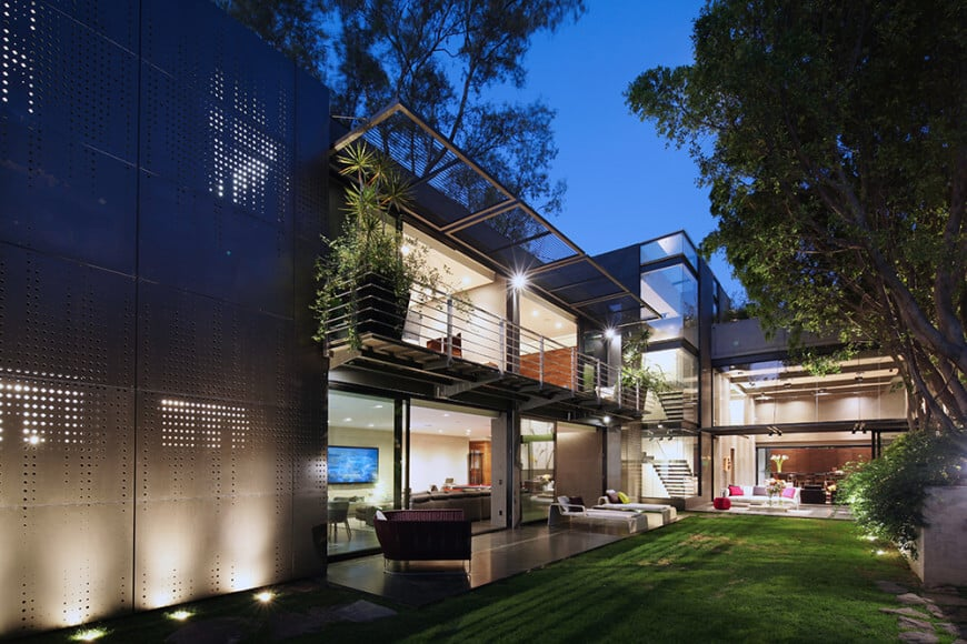 Gorgeous modern house featuring a relaxing patio area near the lawn area.