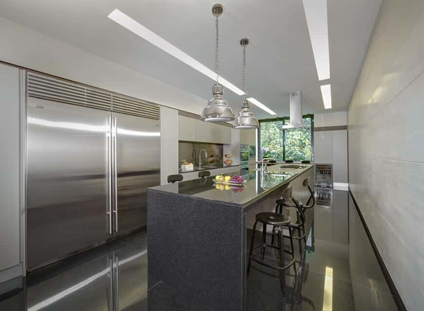 Single wall modern kitchen featuring an island with a breakfast bar lighted by pendant lights and is set on the black tiles flooring.