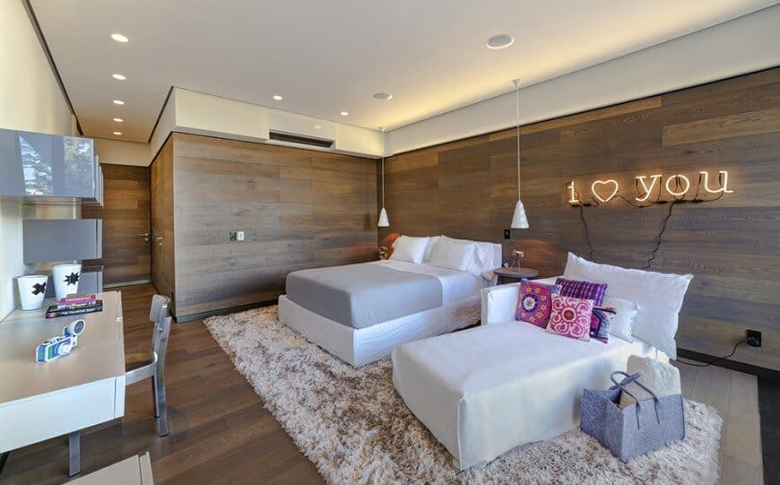 Guest bedroom with wood paneled walls and flooring sporting a cohesive look. It is filled with gray shelves and a floating desk facing the white bed and chaise lounge that's filled with charming pillows.