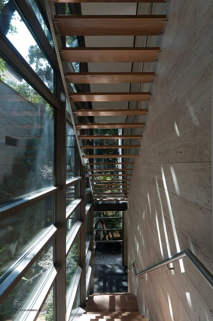 Contemporary wooden straight narrow staircase and landing with steel hand rail.