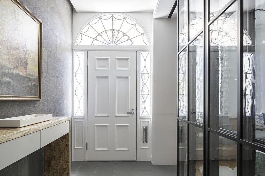 This foyer features tiles flooring and white walls along with its door.