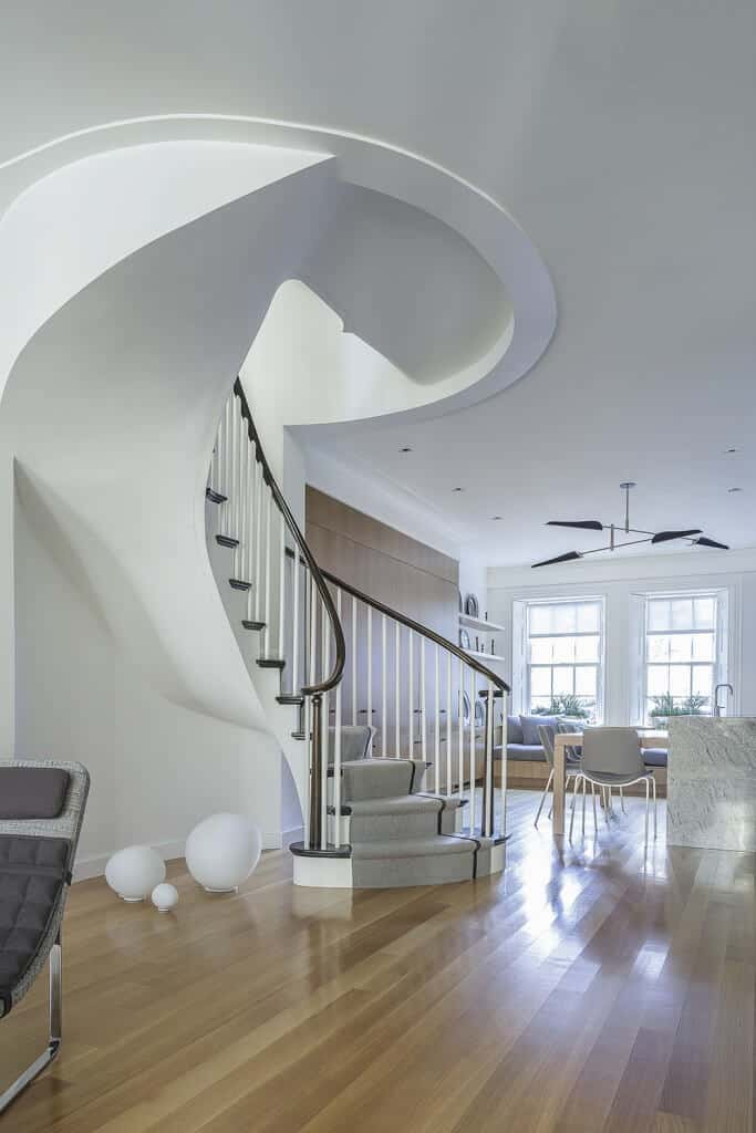 This home boasts a circular staircase with stylish gray carpet floors and white railings.