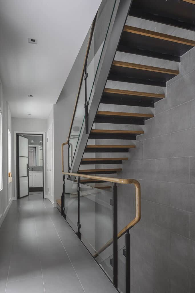 Contemporary home featuring a stylish staircase leading to the home's second floor landing with gray tiles flooring.