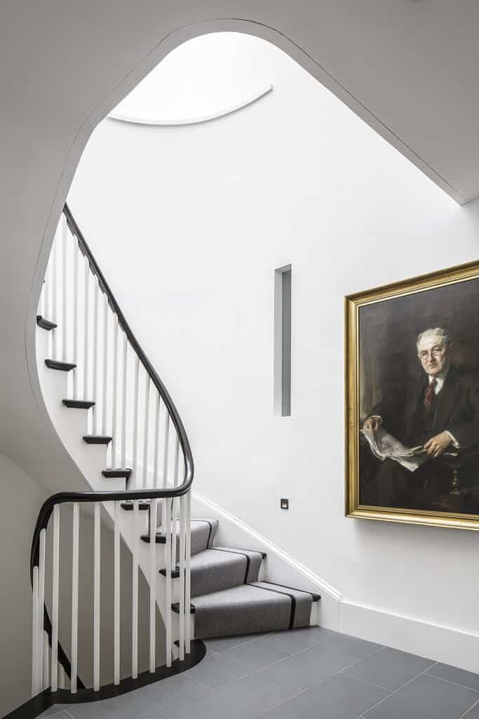 Landing with stylish stair details featuring a portrait artwork and a carpeted staircase.