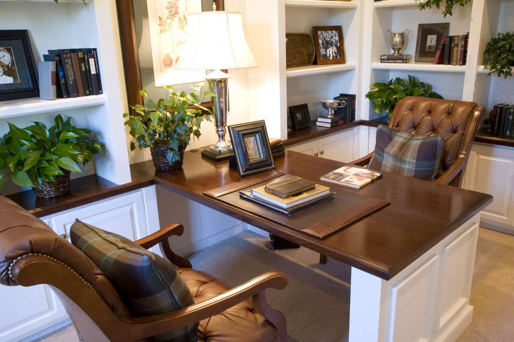 Nicely designed home office with white and brown desk, plants and shelving.