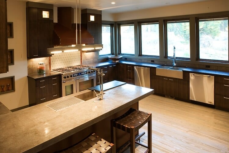 This kitchen offers a narrow center island with a marble countertop. The island is set on a hardwood flooring. The space is being lighted by recessed ceiling lights.