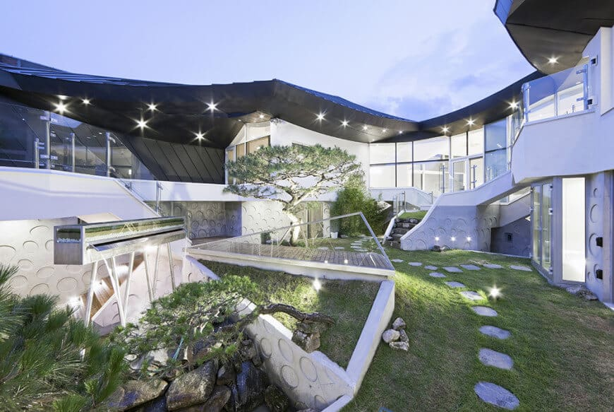 This home is absolutely stunning with its garden area and its lighting illuminating the outdoor area like stars.