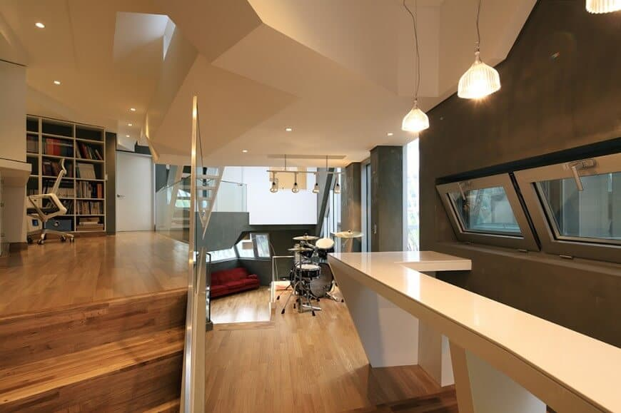 Contemporary open floor plan home with a wooden staircase framed with glass railing and leads to the corner home office boasting a modern chair and desk.