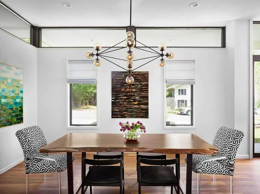A dining room surrounded by white walls and hardwood flooring. It features a wood top dining table and classy chairs lighted by captivating ceiling lighting.