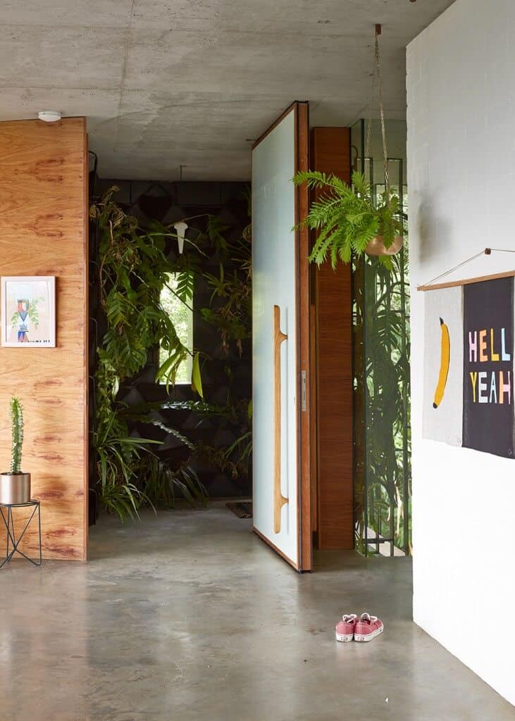 A foyer with concrete flooring and rustic ceiling is decorated with indoor plants and wall art pieces.